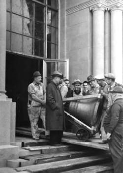 Hoover Library director Ralph Lutz (second from left) watches workmen bring the bells into Hoover Tower, 1941. Hoover Institution Archives.