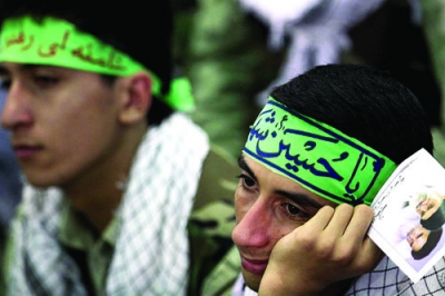 Members of the Basij listen as Ayatollah Ali Khamenei speaks