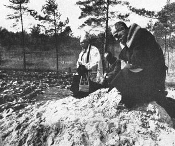 Father Stanislaw Jasinski, representative of the bishop of Krakow, prays over the mass graves